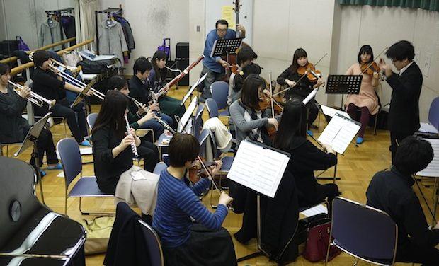 Yusuke Ichihara conducting NJBP in a small rehearsal room.